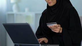 Número de tarjeta de crédito de inserción femenino musulmán sonriente en el ordenador portátil, haciendo compras en línea almacen de metraje de vídeo