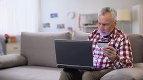 Número de tarjeta de crédito de inserción masculino jubilado en el ordenador portátil, uso en línea del pago metrajes