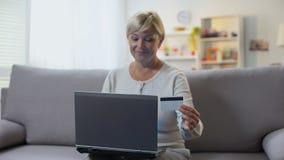 Número de tarjeta de crédito que entra en el sofá que se sienta del ordenador portátil, pago de la mujer rubia madura almacen de video