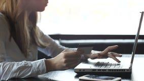 Número de tarjeta de crédito que entra de la mujer joven en el ordenador portátil, pagando facturas de servicios públicos en líne almacen de metraje de vídeo