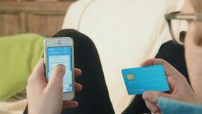 Número de tarjeta de crédito de relleno del hombre joven en su smartphone que paga compras en línea almacen de video