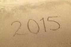 Número del año 2015 escrito en la playa arenosa Imagen de archivo libre de regalías