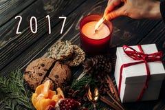 número del Año Nuevo de la muestra de 2017 textos con la mano que se enciende encima de vela y Fotografía de archivo libre de regalías