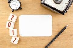 Número del Año Nuevo del rojo 2017 en la sobremesa de madera con la tarjeta de papel, ala Fotografía de archivo libre de regalías