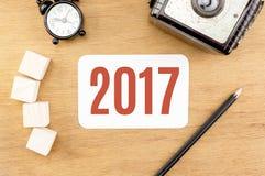 Número del Año Nuevo del rojo 2017 en la sobremesa de madera con la tarjeta de papel, ala Foto de archivo