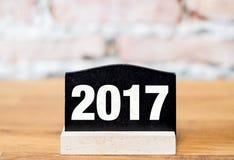 Número del Año Nuevo 2017 en muestra de la pizarra en la tabla de madera en el ladrillo w Fotos de archivo
