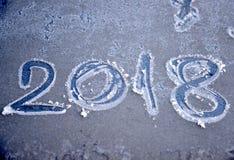 Número del Año Nuevo 2018 sobre el vidrio escarchado del coche Foto de archivo libre de regalías