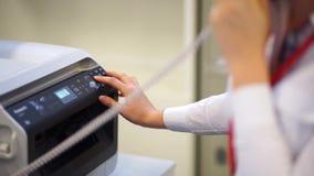 Número discado da mão da mulher no telefone no escritório video estoque