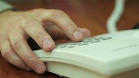 Número discado da mão do homem de negócios no telefone no escritório filme