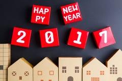 Número do ano novo feliz 2017 em cubos vermelhos da caixa de papel e no archi home Fotografia de Stock