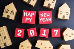 Número do ano novo feliz 2017 em cubos vermelhos da caixa de papel e no archi home Foto de Stock Royalty Free