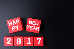 Número do ano novo feliz 2017 em cubos vermelhos da caixa de papel no backg preto Imagens de Stock
