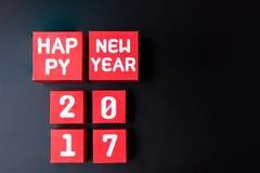 Número do ano novo feliz 2017 em cubos vermelhos da caixa de papel no backg preto Foto de Stock Royalty Free