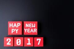 Número do ano novo feliz 2017 em cubos vermelhos da caixa de papel no backg preto Fotografia de Stock Royalty Free