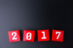 Número do ano novo feliz 2017 em cubos vermelhos da caixa de papel no backg preto Imagem de Stock Royalty Free