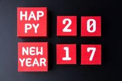Número do ano novo feliz 2017 em cubos vermelhos da caixa de papel no backg preto Fotografia de Stock