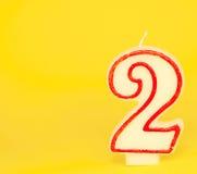 Número duas velas no fundo amarelo Fotos de Stock Royalty Free