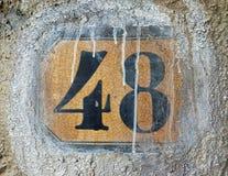 Número 48 em uma telha em uma parede, listada com pintura branca fotografia de stock royalty free
