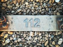 Número 112 en la barrera de piedra Fotos de archivo libres de regalías