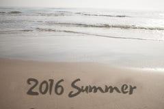 Número 2016 escrito à mão na areia do litoral Foto de Stock Royalty Free