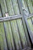 Número 7 escrito em uma porta verde resistida velha Foto de Stock