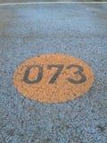 Número 073 escrito en el camino de la pista de despeque Imágenes de archivo libres de regalías