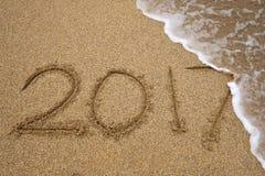 Número 2017 escrito en la arena de la costa Imagen de archivo libre de regalías