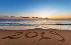 Número 2019 escrito en la arena de la costa en la salida del sol imagen de archivo