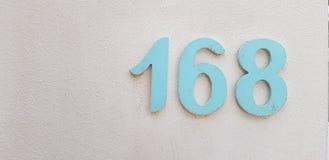 Número 168 na parede pintada branca imagens de stock royalty free