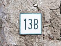 Número 138 na parede velha Imagens de Stock