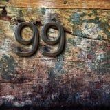 Número 99 no fundo de madeira Fotografia de Stock Royalty Free