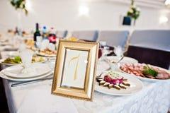 Número 7 no quadro na tabela do convidado no copo de água Fotografia de Stock Royalty Free