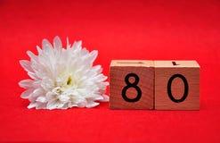 Número ochenta con una margarita blanca fotos de archivo