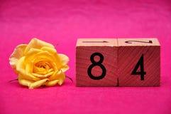 Número ochenta y cuatro con una rosa amarilla imagen de archivo libre de regalías