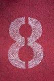 Número oito na pista de atletismo Número branco da trilha na pista de borracha vermelha Foto de Stock