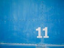 Número once en blanco con el fondo y los remaches azules Fotografía de archivo