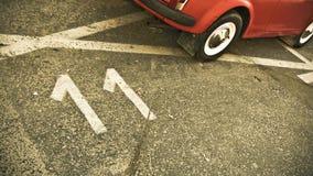 Número once pintado en el camino con el coche rojo Foto de archivo