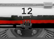 Número 12 pela máquina de escrever velha no Livro Branco Fotos de Stock
