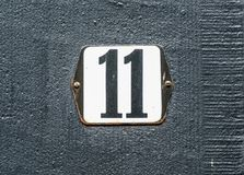 Número preto do número da casa 11 na placa branca Fotografia de Stock