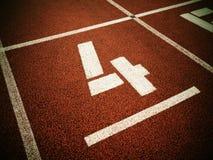 Número quatro Número branco da trilha na pista de borracha vermelha, Imagens de Stock