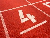 Número quatro Número branco da trilha na pista de borracha vermelha, Imagem de Stock