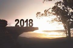 número 2018 que se coloca al borde del acantilado con los árboles Fotografía de archivo