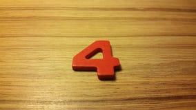 Número rojo 4 en fondo de madera Fotografía de archivo libre de regalías