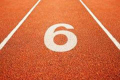 Número seis na pista de atletismo Imagens de Stock Royalty Free