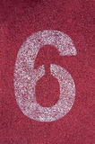 Número seis na pista de atletismo Número branco da trilha na pista de borracha vermelha Imagem de Stock Royalty Free
