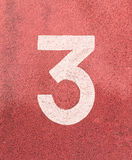 Número três, número branco da trilha na pista de borracha Fotos de Stock