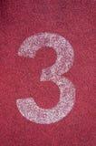 Número três na pista de atletismo Número branco da trilha na pista de borracha vermelha Fotografia de Stock Royalty Free