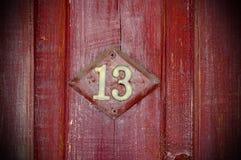 Número trece en el fondo de la puerta roja imagen de archivo libre de regalías