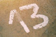 Número trece -13 en el piso concreto Imágenes de archivo libres de regalías