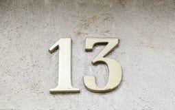 Número trece en una pared Imagenes de archivo